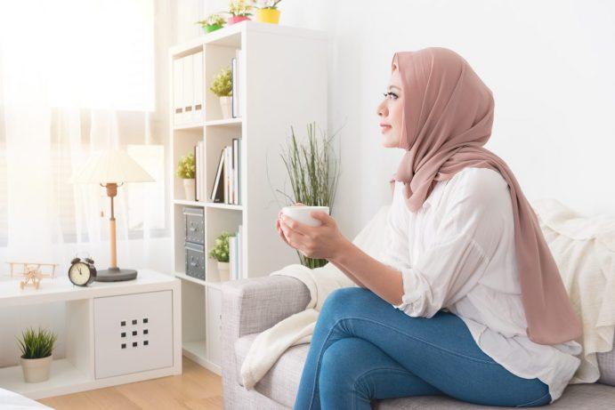 woman wearing head scarf drinking tea in comfortable home