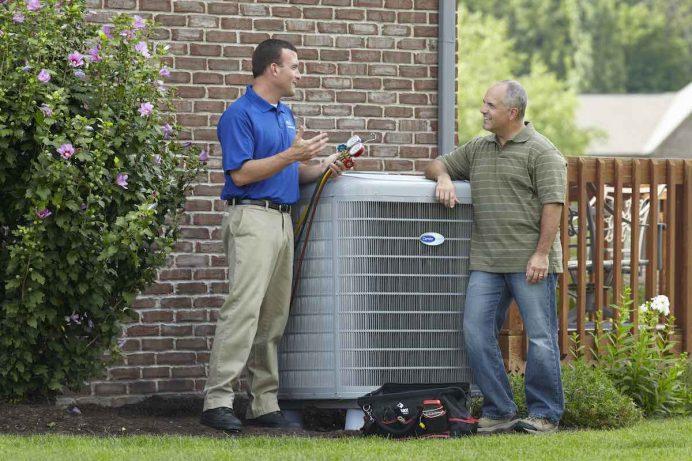 Homeowner and repairman discuss routine HVAC maintenance