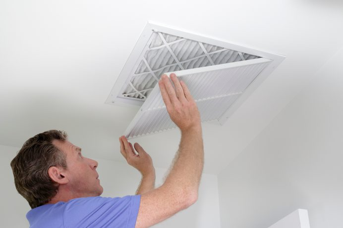 middle aged man installing a filter to hvac unit
