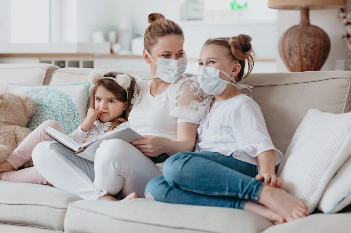 mom and her two daughters wearing respirator masks at home